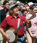 "Photo byPhil Grout..Jim Haner strolls up a jam-packed Main St. and entertains the crowd.with a bit of ""breakdown"" banjo music during the Flower and Jazz Festival."