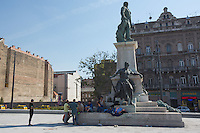 Illegal migrants take a rest next to a statue close to a transit zone at the main railway station Keleti in Budapest, Hungary on August 30, 2015. ATTILA VOLGYI