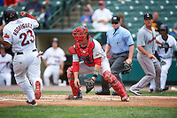 Pawtucket Red Sox catcher Matt Spring (47) waits for a throw as Reynaldo Rodriguez (23) runs towards home plate to score a run during a game against the Rochester Red Wings on July 1, 2015 at Frontier Field in Rochester, New York.  Umpire Sean Barber and pitcher Steven Wright are seen in the background.  Rochester defeated Pawtucket 8-4.  (Mike Janes/Four Seam Images)