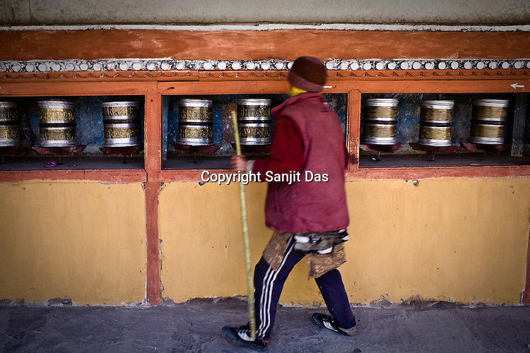 A Buddhist man preys while he moves the prayer wheels at the age-old Hemis Monastery in Leh, Ladakh, India.