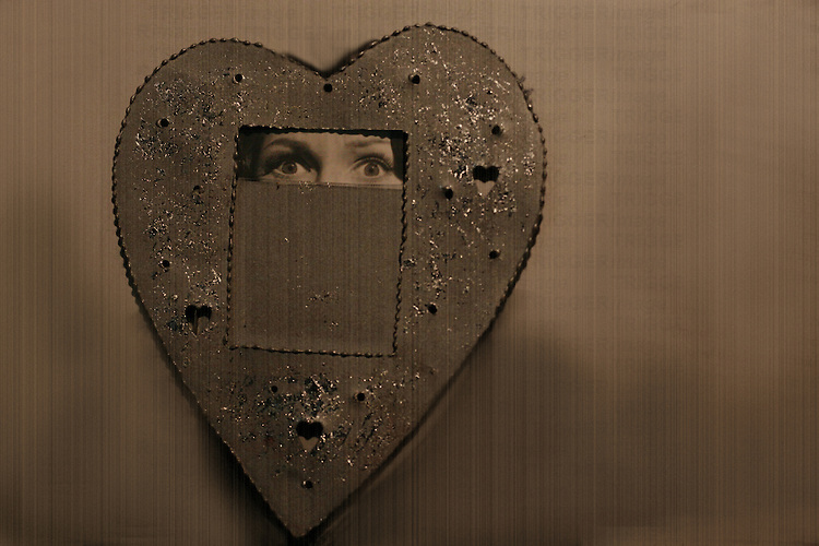 A woman peering through a heart