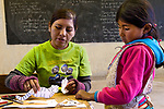 Andean Mountain Cat (Leopardus jacobita) biologist, Alejandra Rocio Torrez Tarqui, showing girl how to put together Andean cat cut out during an educational outreach program, Ciudad de Piedra, Andes, western Bolivia