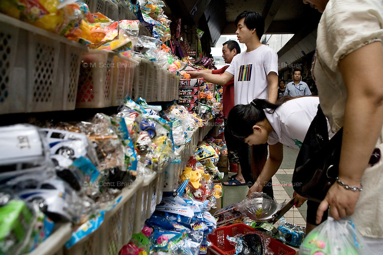 Shoppers browse toys and other plastic goods at a wholesale market in the Fuzi Miao area of Nanjing, Jiangsu, China.  The market acts as a distributor of consumer goods to shops and smaller markets throughout the city.