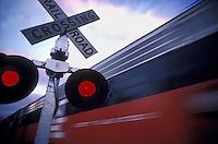 Passenger train speeds through a railroad crossing