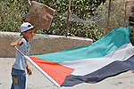 A young Palestinian boy waves the Palestinian flag during a non-violent demonstration against Israel's controversial separation barrier in the West Bank town of Beit Jala, near Bethlehem on 11/07/2010.