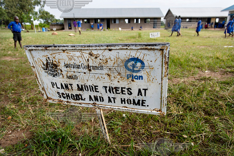 A sign at on the grass at Agwait Primary School reads: 'Plant more trees at school and at home.'