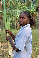 Lexcine Yunkaporta gathering pandanus leaf, Aurukun, Cape York Peninsula.