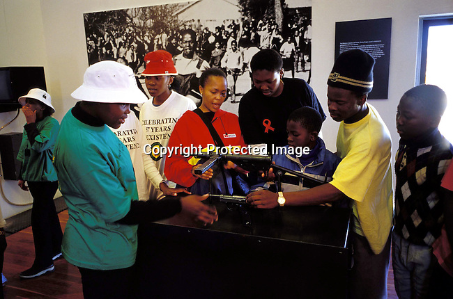 digasow00091.South African Places. Gauteng. Unidentified people looking at homemade guns in the newly opened Hector Peterson museum on June 14, 2002 in Soweto, South Africa. Hector Peterson was killed during the student uprising in Soweto in 1976, where black students demonstrated against the Afrikaans language imposed by them by the Apartheid government. The new museum opened on Youth Day June 17, 2002..©Per-Anders Pettersson/iAfrika Photos