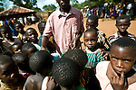 Local children swarm a man handing out cups of water during a celebration of the parish priest's 25th year being ordained in Lukeleli, Tanzania on November 16, 2008, a day where temperatures pushed well beyond 100 degrees Fahrenheit. The town had initially dug their wells too deep and due to a dry early rainy season they were not pumping correctly leaving most of the town to drink water that had come from much more shallow sources. This water has a much higher chance of being infected with animal runoff and other sources of neglected tropical diseases.