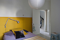 A signature wall of mustard yellow sets the decorative theme of the main bedroom