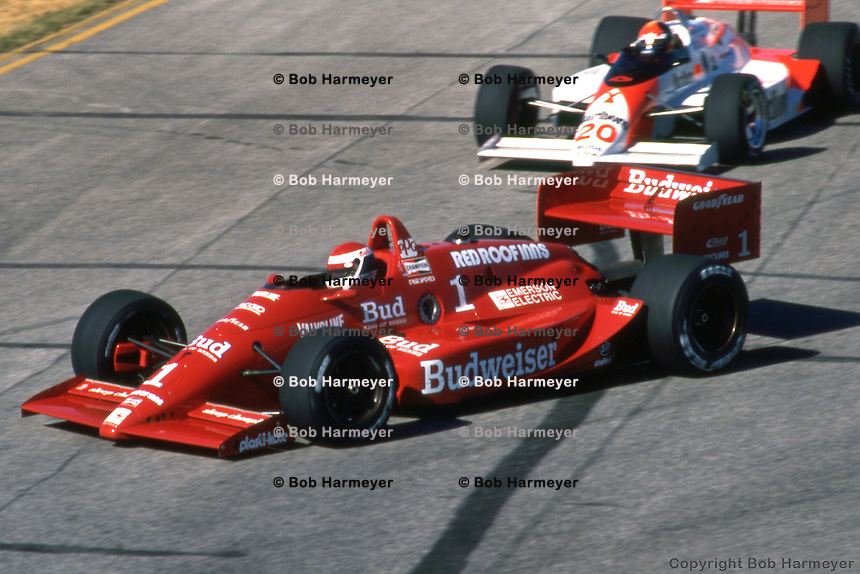 Bobby Rahal drives his Lola T88/00/Judd ahead of Emerson Fittipaldi during the Budweiser Cleveland Grand Prix on July 3, 1988, on the temporary circuit at Burke Lakefront Airport in Cleveland, Ohio.