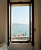 ITALY, Garda, view of man and woman relaxing by Lake Garda from a window of the Hotel Locanda San Vigilio.