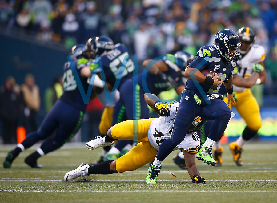 Russell Wilson #3 of the Seattle Seahawks evades a tackle on the run from Bud Dupree #48 of the Pittsburgh Steelers in the second half during the game at CenturyLink Field on November 29, 2015 in Seattle, Washington. (Photo by Jared Wickerham/DKPittsburghSports)