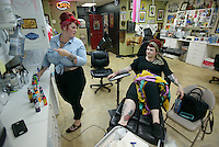 Brie Felts chats with Valerie Gunther while preparing to tattoo her leg at Primal Instinct Tattoo. Photo by James R. Evans