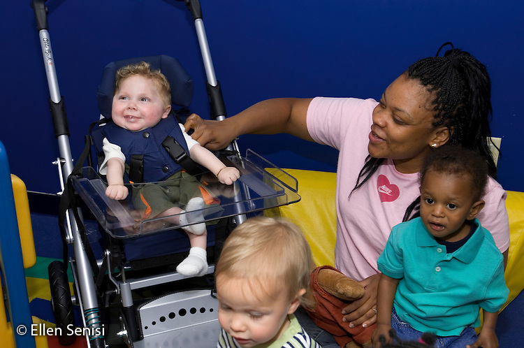 MR / Schenectady, NY.Schenectady Day Nursery / private non-profit daycare center / Infant Class.Caregiver (African-American) and toddlers interact with infant. (boy, 1, cerebral palsy) - (Child is sitting in pediatric stroller - style manual wheelchair).MR: Did1, AF-SDNI.© Ellen B. Senisi