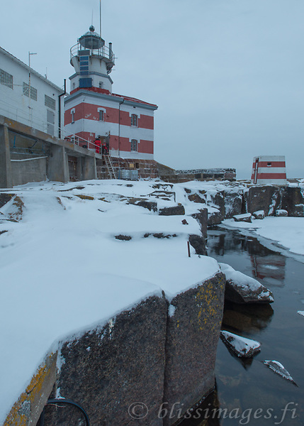Workmen enter Märket lighthouse after early December snowfall.