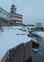 Workmen enter Märket lighthouse after early December snowfall.