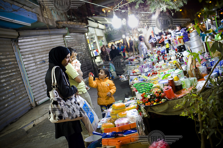 People enjoy a night out in the Karadah district of Baghdad. A recent attack in a church and bombings didn't stop many people going out in the evening. A woman and her family shop at a street market.