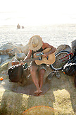 USA, California, San Diego, a man plays the guitar while sitting by the rocks on Ocean Beach