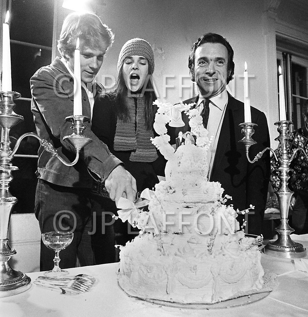 """January 1970, New York City. American actor Ryan O'Neal, American actress Ali MacGraw, and Canadian director Arthur Hiller cutting a wedding cake on the movie set of the 1970 American film """"Love Story"""". O'Neal starred as Oliver Barrett IV and MacGraw as Jennifer Cavilerri in the romance directed by Hiller."""