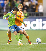 Seattle Sounders FC forward Fredy Montero, left, tangles with Houston Dynamo defender Andre Hainault during play  at Qwest Field in Seattle Friday March 25, 2011. The match ended in a 1-1 draw.