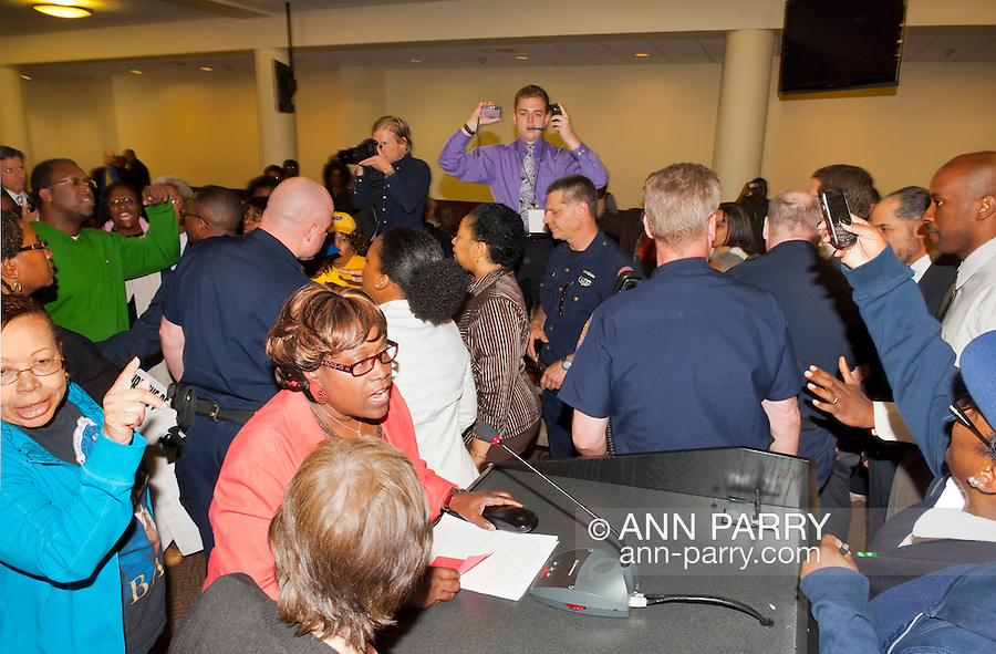 MAY 9, 2011 - MINEOLA, NY: Nassau County Police Officers called to scene of protest during public hearing of Nassau County Legislative proposed Redistricting. Entering scene upper right in white shirt, Legislator Kevan Abrahams of LD 1, Hempstead. At podium in orange, Regis Lawrence Thompson of Hempstead, who shortly before had refused to leave when told to do so by (not seen here) MAY 9, 2011 - MINEOLA, NY: Nassau County Police Officers called to scene of protest during public hearing of Nassau County Legislative proposed Redistricting. Seen from back and wearing green sweater, Ramel Smith of Hempstead holding hand over (out of view) his young son in front of him. The police officers were already in the building. Recess was called when Regis Lawrence Thompson at podium was told by Nassau County Presiding Officer Peter Schmitt that the man called to speak could not give Thompson his turn, though people had given their turn to others earlier, and Thompson refused to give up microphone. No arrests. At Nassau County Executive and Legislative Building, 1550 Franklin Avenue, Mineola, New York, USA on May 9, 2011. Seen at left at back (in green sweater) Ramel Smith of Hempstead. At Nassau County Executive and Legislative Building, 1550 Franklin Avenue, Mineola, New York, USA on May 9, 2011