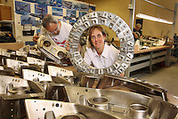 ANNE SHYBUNKO-MOORE, President of GSE DYNAMICS, Inc., an aircraft parts manufacturing company founded by her father.  She poses inside a welding fixture for Apache helicopter exhaust ducts.  In front of her are C-5 fire shield engine detail, made of titanium.  Aircraft bench mechanics Sam Rodriguez and Rich Esposito are behind her.  25 Corporate Dr., Hauppauge.  Newsday/ARI MINTZ  1/9/2008.