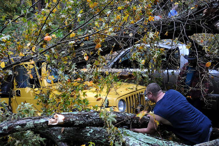 TORRINGTON CT, 07 OCT 13- 100713AJ01- Tim Therrien and Donald O'Brien, both of 124 Mountain Ave., in Torrington check out their vehicles after a swamp maple fell during a storm Monday crushing them both. Therrien's 2004 Jeep Wrangler was nearly split down the middle and O'Brien's 2001 Chevy Silverado was crushed by the tree that fell at about 5 p.m.  Alec Johnson/ Republican-American
