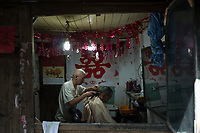 Gaomiao township, Meishan, Sichuan province, China, October 2014 - An elderly man has a haircut.
