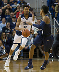 Nevada forward Jordan Brown (21) dribbles past Akron's guard Loren Cristian Jackson (1) in the first half of an NCAA college basketball game in Reno, Nev., Saturday, Dec. 22, 2018. (AP Photo/Tom R. Smedes)