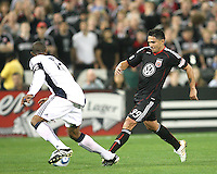 Jaime Moreno #99 of D.C. United slots a pass away from Cory Gibbs #12  of the New England Revolution during an MLS match on April 3 2010, at RFK Stadium in Washington D.C.