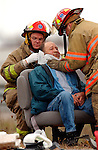 De Pere firefighters help a man at the scene of a wreck on U.S. 41 at the County EE overpass in De Pere on Monday, November 1, 2004. One person died and several were injured in the three vehicle accident.