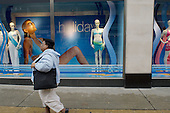 An overweight Afro-caribbean woman walks past a Marks & Spencer window display of swimwear in Oxford Street, London.
