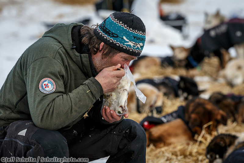 Norwegian musher Geir Idar Hjelvik eats a heated meal while resting at the Ruby Checkpoint during the 2016 Iditarod.  March 11, 2016    <br /> <br /> Photo by Jeff Schultz (C) 2016  ALL RIGHTS RESERVED