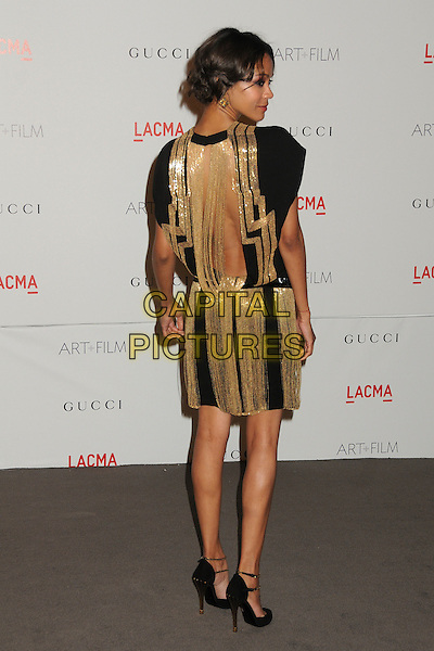 Zoe Saldana.The Inaugural Art and Film Gala held at LACMA in Los Angeles, California, USA..November 5th, 2011.full length gold black dress tassels fringed belt backless looking over shoulder back behind rear .CAP/ADM/BP.©Byron Purvis/AdMedia/Capital Pictures.