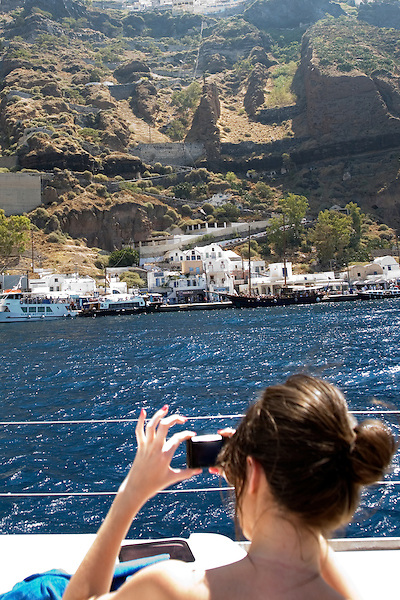 A women takes a picture of Skala Pier, the old Port of Santorini, while sailing south in Santorini, Greece on July 5, 2013.