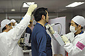 February 20 , 2012, Fukushima, Japan - A worker at the Fukushima No. 1 Nuclear Power Plant, center, undergoes a radiation measurement check after finishing his shift at the plant, on Feb. 20, 2012, in Okuma, Fukushima Prefecture.