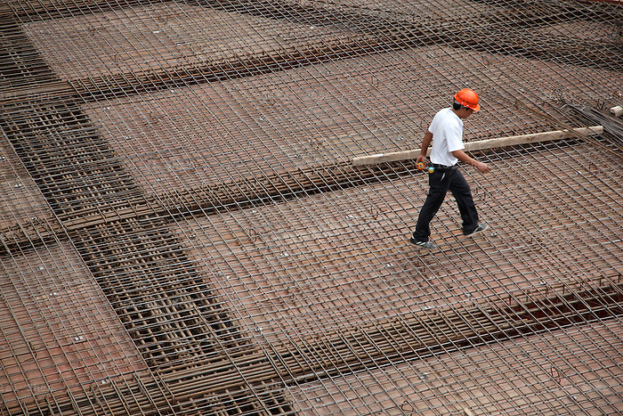 A worker walks on top of steel re-bars at a construction site in Shanghai, China on 29 September 2009.