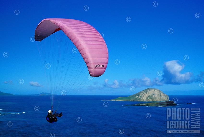 A man enjoys paragliding near Rabbit island (Manana Isl.) and Makapuu pt. on Oahu's eastern coastline.