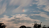 Rainbow cloud above southern England.  The rainbow is seen when light reflects off tiny ice crystals inside the body of the cloud's water vapour.