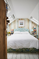 In the attic bedroom, natural materials are mixed with cheerful colour such as the painted wooden timbers that provide a backdrop to the double bed. Several Velux windows provide plenty of light.