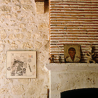 A collection of small ceramic figures and a small painting on the stone mantelpiece
