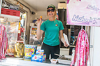 Hard working woman packaging mini doughnuts in her food booth. Grand Old Day Festival. St Paul Minnesota MN USA