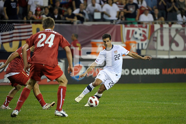 US midfielder Benny Fielhaber (22) maneuvers to evade Poland defender Dariusz Pietrasiak (24).  The U.S. Men's National Team tied Poland 2-2 at Soldier Field in Chicago, IL on October 9, 2010.