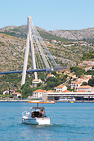 The new Dubrovnik Franjo Tudman Franja Tudmana suspension bridge at the entrance to Gruz docks harbour, Rijeka Dubrovacka bay and Kanal Daksa canal. A small pleasure motor boat with a big sun shade. Luka Gruz harbour. Dubrovnik, new city. Dalmatian Coast, Croatia, Europe.