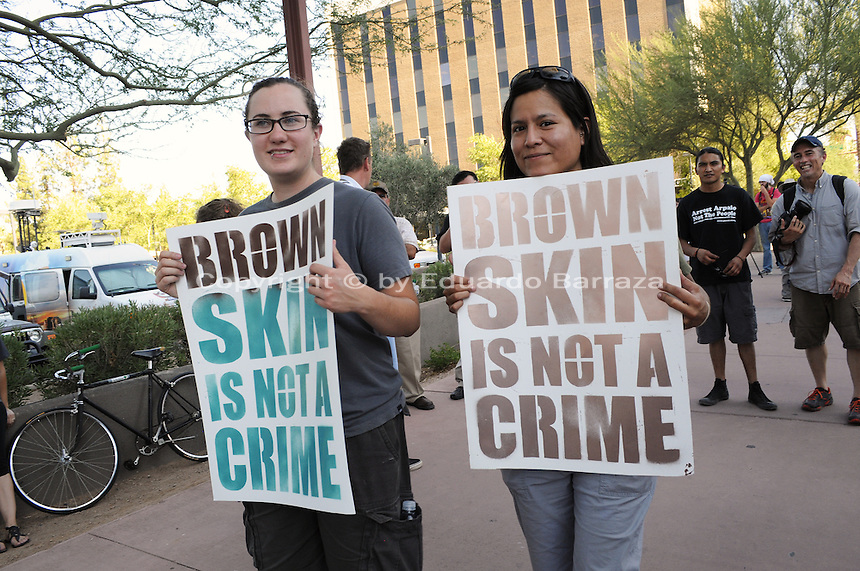 Phoenix, Arizona. June 25, 2012 - Two protesters stand in front of the U.S. Immigration and Customs Enforcement (ICE) building in Phoenix, Arizona show their opposition to SB 1070 law and racial profiling against brown-skinned people. Immigrant rights groups protested the United States Supreme Court ruling on Arizona law for upholding SB 1070's provision that will allow police to demand papers if there's reasonable suspicion that a person may be illegally in the country. Photo by Eduardo Barraza © 2012