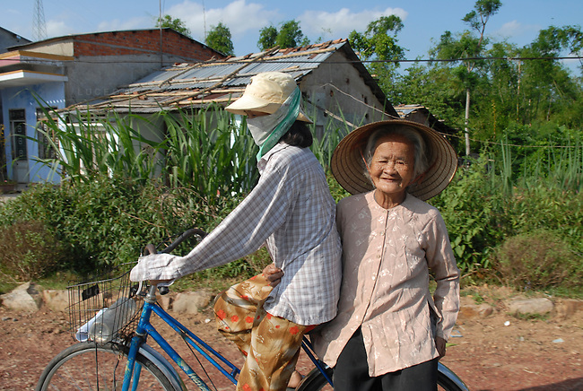 A Vietnamese woman transports her grandmother from the doctor's office back to her home on the back of her bicycle outside of Ho Chi Minh City, Vietnam.