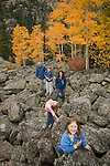 Family pauses for photo after scramble over boulders with golden colors of autumn in aspen stands above, all on a September morning above Bear Lake in Rocky Mountain NP, Colorado
