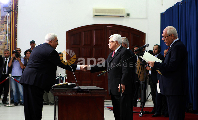 Palestinian National Authority President Mahmoud Abbas and his Prime Minister Salam Fayyad, receive the new government Ministers during the swearing in ceremony of the new cabinet, at Abbas's headquarters in the West Bank town of Ramallah, on 16 May 2012. Abbas said early 16 May 2012 that the incoming government 'will be dismissed immediately' if the political partnership with Hamas is implemented. Photo by Thaer Ganaim