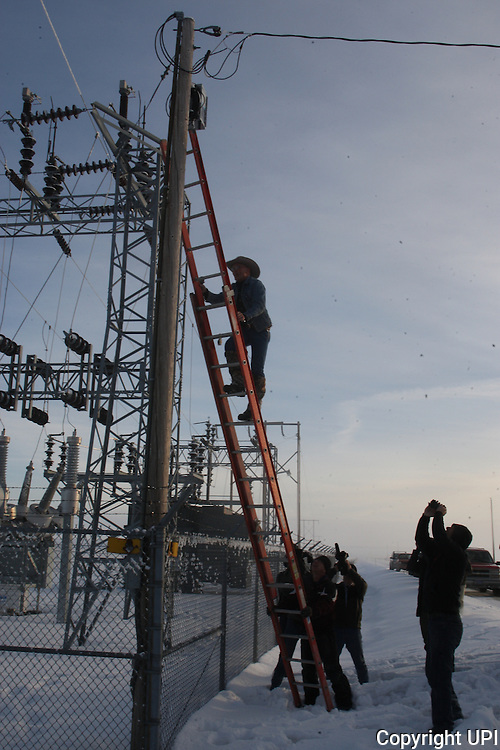 Activists LaVoy Finicum climbs up a ladder to remove FBI surveillance cameras found at a power station near the Malheur National Wildlife Reserve on January 15, 2016 in Burns, Oregon.  Ammon Bundy and about 20 other protesters took over the refuge on Jan. 2 after a rally to support the imprisoned local ranchers Dwight Hammond Jr., and his son, Steven Hammond. Another surveillance camera was found near the reserve.    Photo by Jim Bryant/UPI